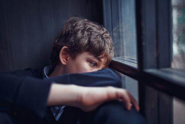 sociala medier påverkan - ledsen pojke vid fönster